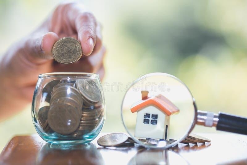 Dinheiro planejando das economias das moedas para comprar um conceito, uma hipoteca e uns organismos de investimento imobiliário  fotos de stock