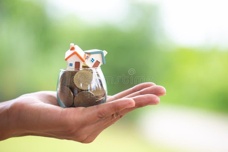 Dinheiro planejando das economias das moedas para comprar uma casa, o conceito para a escada da propriedade, a hipoteca e os orga imagem de stock