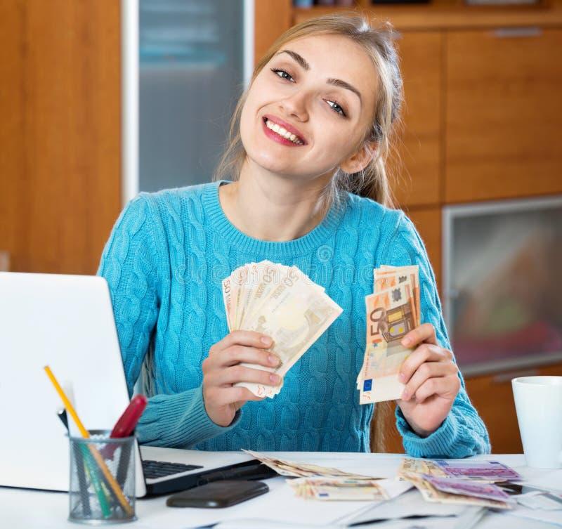 Dinheiro positivo do salário da jovem mulher que é freelancer foto de stock