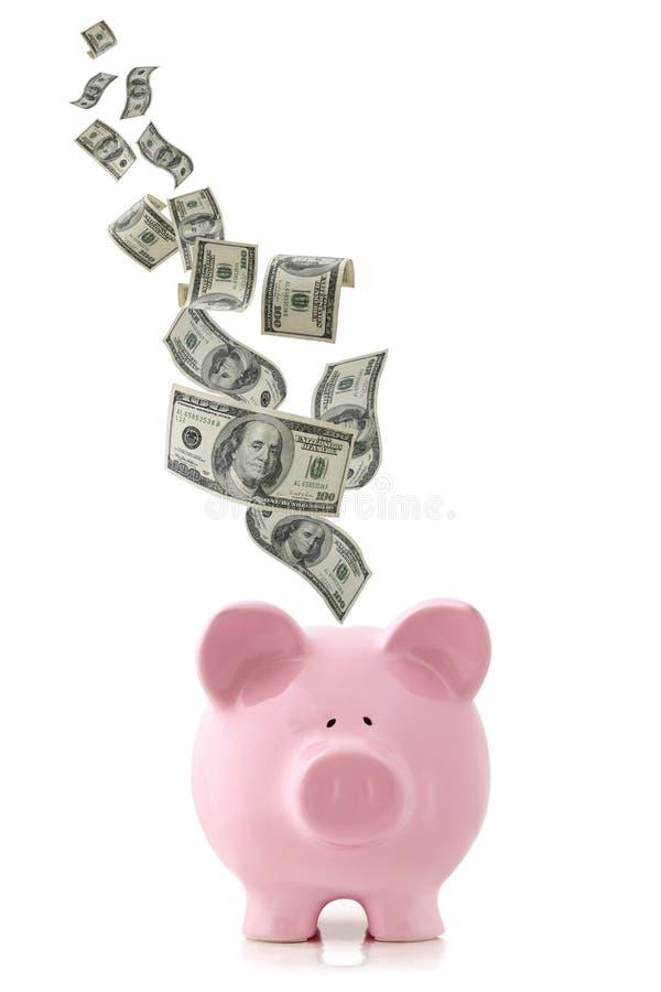 Dinheiro que cai no banco Piggy imagens de stock