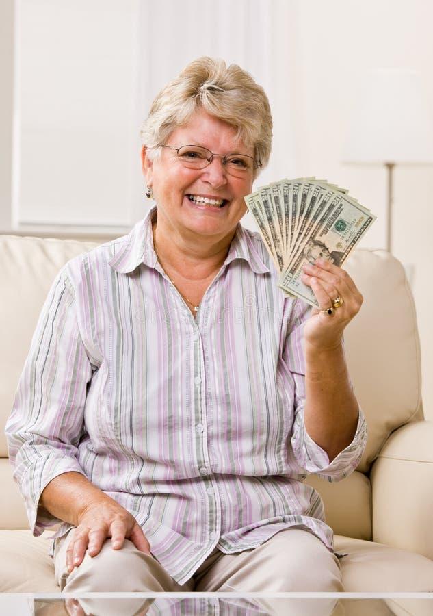 Dinheiro sênior da terra arrendada da mulher fotografia de stock royalty free
