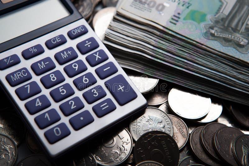 Dinheiro sob a forma das cédulas e das moedas com calculadora fotografia de stock