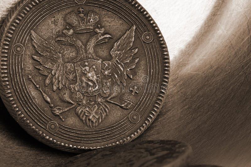 Dinheiro velho de Rússia do século XVII em um fundo de prata metálico, moedas de cobre velhas com uma águia dobro-dirigida imagem de stock royalty free