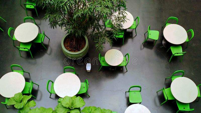 Dining area with green motif in urban mall - high angle view - no people royalty free stock photos