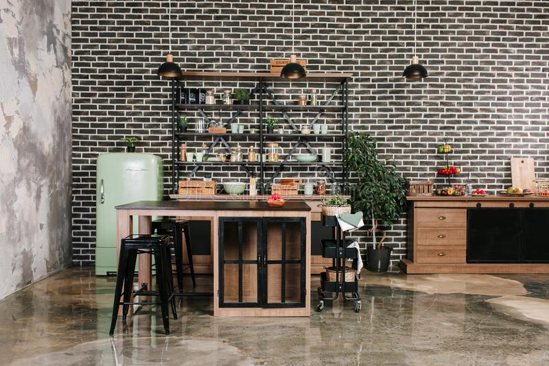 Dining area in industrial style with table, chairs and mint retro fridge. Black vintage brick wall background royalty free stock image