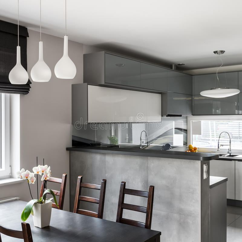 Dining area and kitchen combined. Wooden dining set and pendant lamp, bright grey open kitchen in the background royalty free stock image