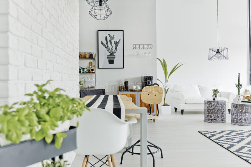Dining area of modern loft. Well-lighted dining area of modern and sapcious loft royalty free stock photos