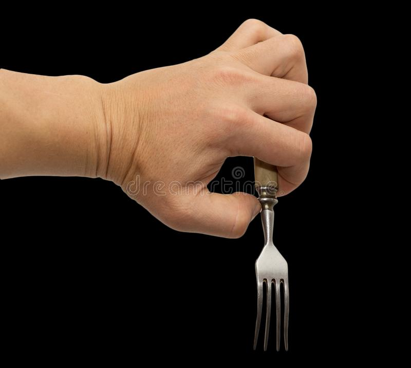 Dining fork in hand on a black background stock photos