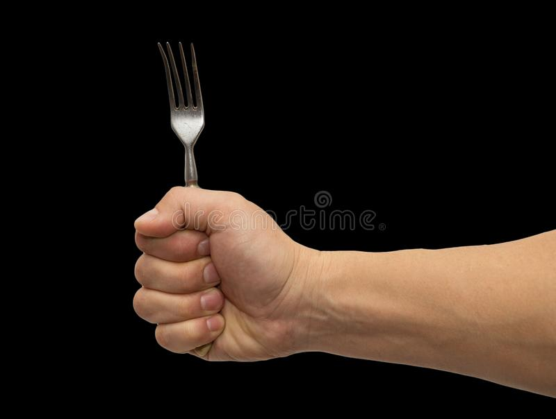 Dining fork in hand on a black background royalty free stock photography