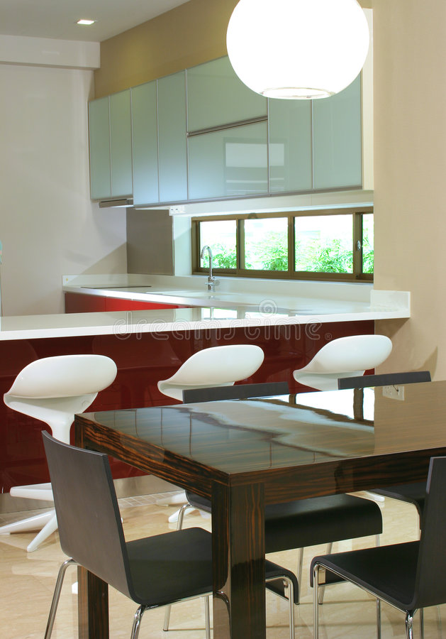 Dining and kitchen. 6 seaters dining table and modern design kitchen royalty free stock photos