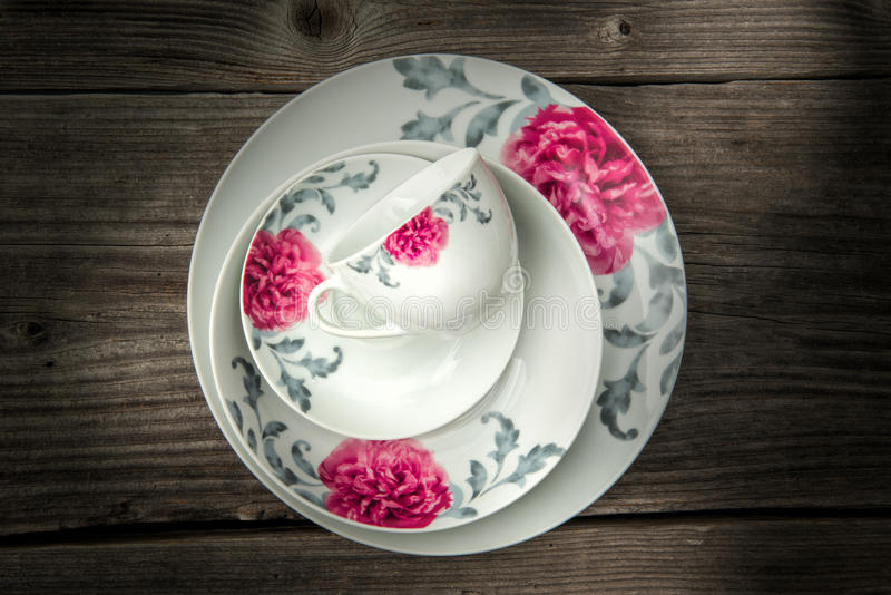 Dining porcelain set of plates and one cup with floral ornament on wooden background, product photography.  stock photos