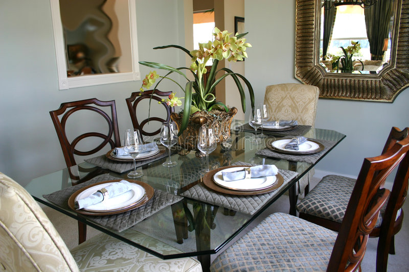 Dining room. Formal dining room with glass table, upholstered chairs, placemats,napkins, holders,mirror and picture on blue wall, and yellow orchids in bronze royalty free stock photography