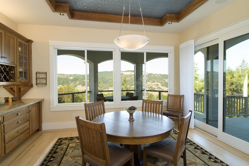 Dining room. With a view, table and chairs,rug,windows,light,cabinets royalty free stock photos