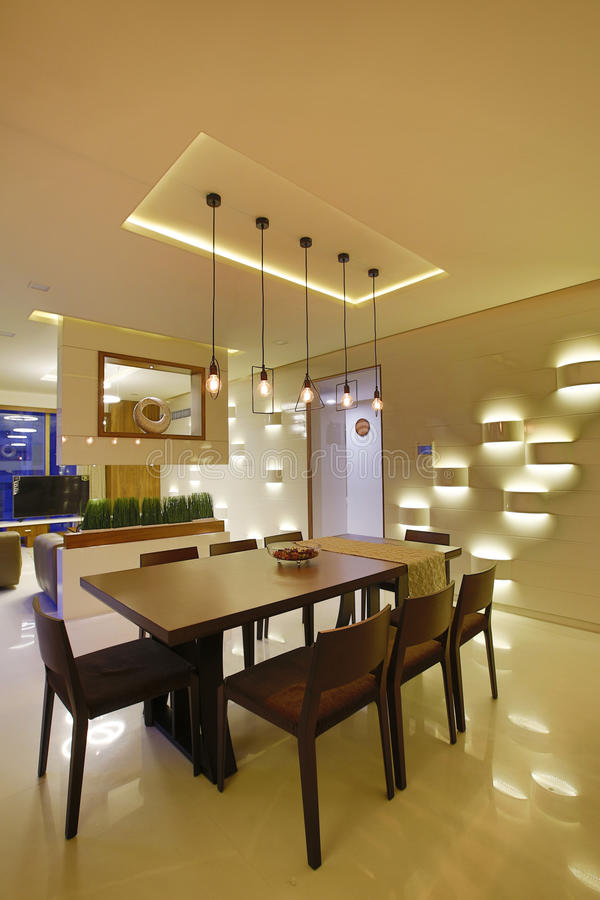 Dining room in Calicut, India. Wooden table and chairs with modern lighting in dining room designed by Amar Architecture and Designs Pvt, Ltd in Calicut, India royalty free stock images