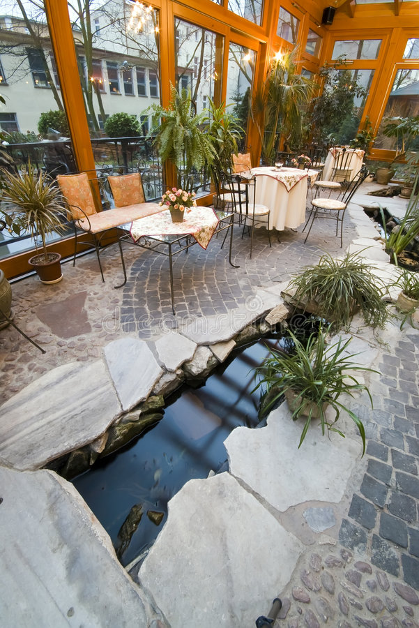 Dining room conservatory. Elegant hotel dining room in conservatory, glass roof, green plants. Stone floor detail with water stream stock photos