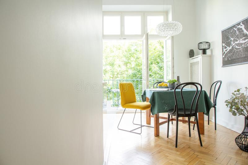 Dining room interior with wooden furniture,white walls, copy space and wide open glass door to balcony royalty free stock photography