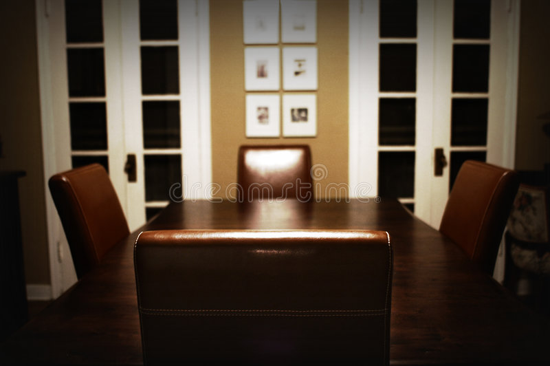 Dining Room Table. Dining room with a wooden table with four leather chairs royalty free stock photo
