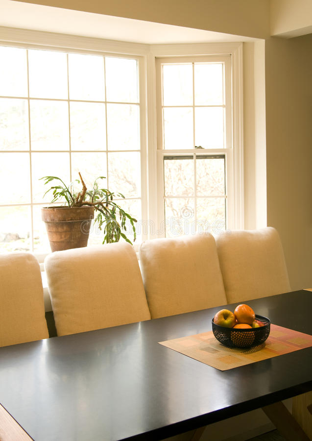 Dining room table with fruit bowl. Dining room table bathed in natural light from bay window with fruit bowl stock photography