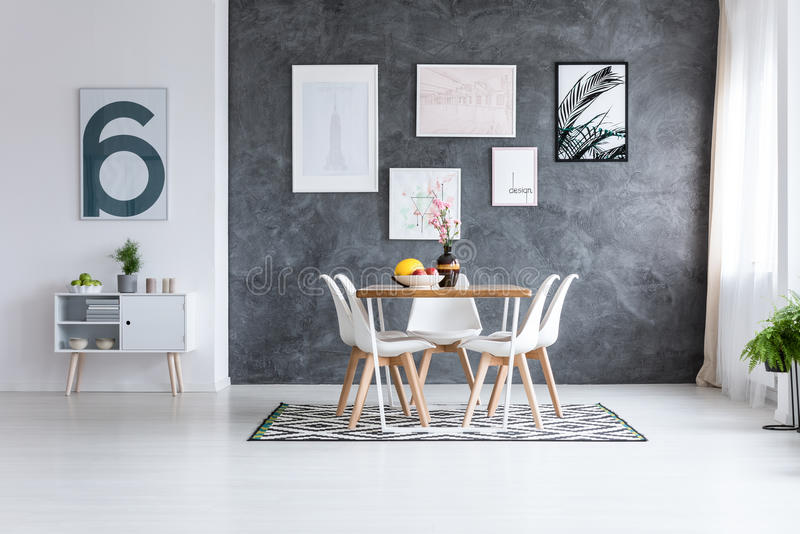 Dining room with white cupboard. Monochromatic dining room with white cupboard against white wall and pictures on dark wall stock images