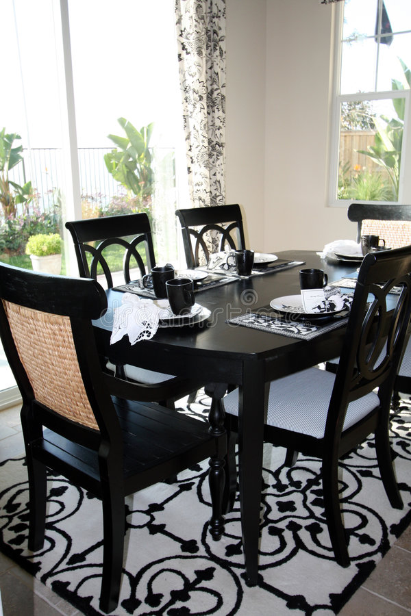 Dining set in B&W - vertical. Vertical view of an upscale formal dining room is done in trendy black and white. Dining table is on a white and black area rug stock images