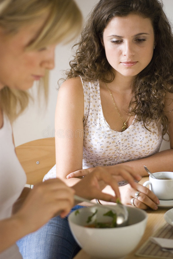 At the dining table. A young woman watching as another prepares meal royalty free stock photos