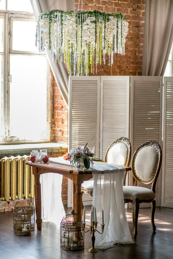 Dining table with classic chairs, flower chandelier, fruit and succulents in the loft space with flowers, side view. Dining table with classic chairs, flower royalty free stock images