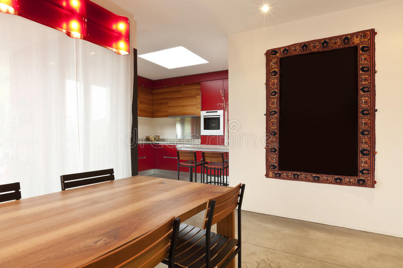 Dining table, kitchen in background. Comfortable modern apartment, dining table, kitchen in background stock photos