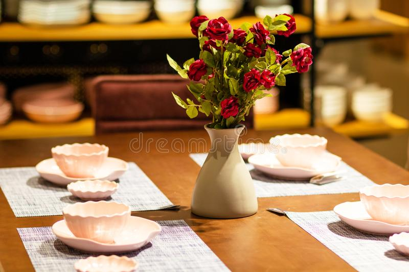 The vase with rose flowers on the table. There were dishes and vases with roses on the table stock photography