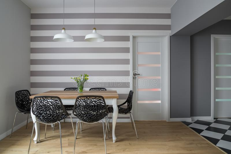 Dining table and openwork chairs. Modern dining room with wooden table, openwork chairs and striped wall stock illustration