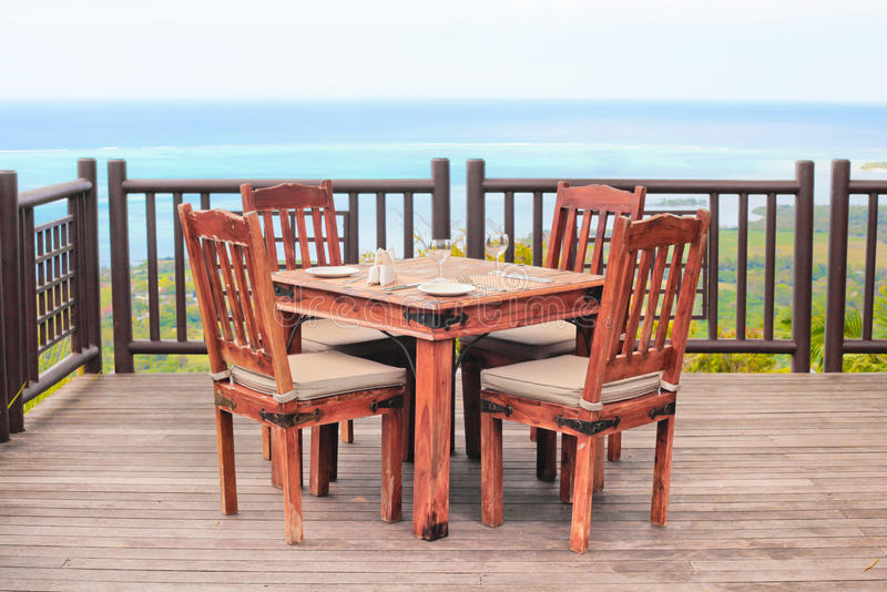 Dining table. Outside dining table and chairs on a wooden balcony stock photos