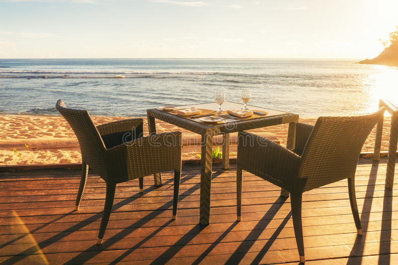 Dining table and two chairs on decking by sea side at evening sun light stock images