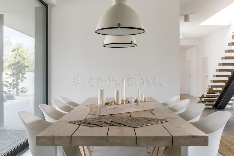 Dining table and white chairs. Room with wood dining table, white chairs and industrial lamp stock photography