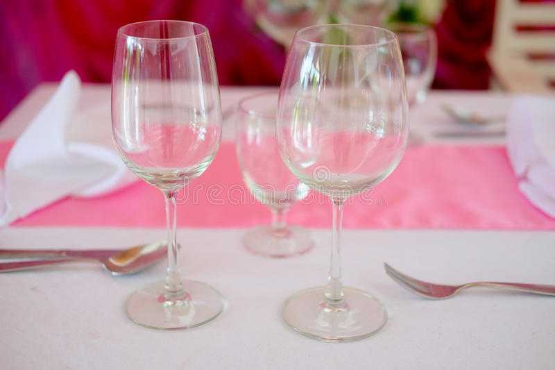Dining table with wine glasses. And pink tablecloth ready for guests royalty free stock images
