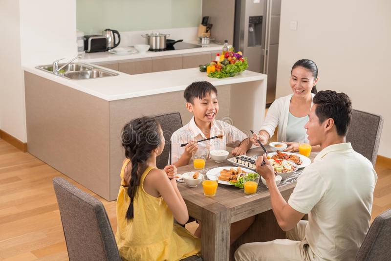 Dining together. Asian family dining together in the kitchen royalty free stock images