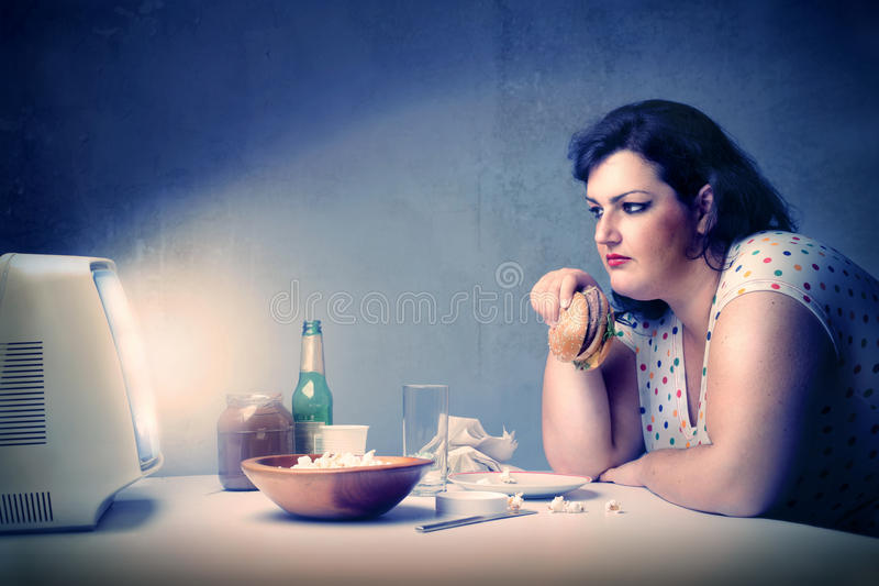 Dinner. Fat woman having dinner with junk food while watching the television stock photography