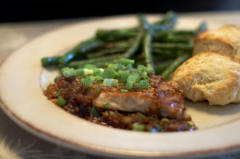 Dinner. Pork chops, buttermilk biscuits, and green beans royalty free stock photos