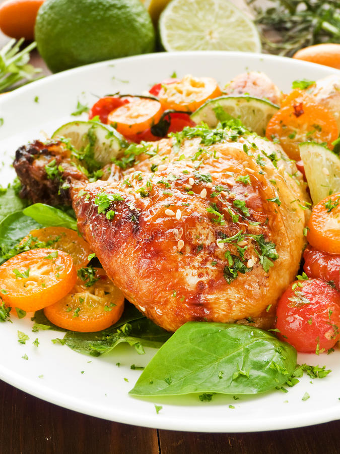 Dinner. Roasted chicken with stir-fry vegetables, fruits and herbs. Shallow dof stock photo