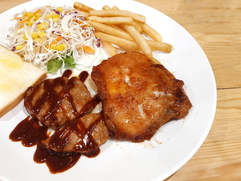 DinnerBBQ pork steak with grilled chicken steak at a shop in Thailand royalty free stock photos