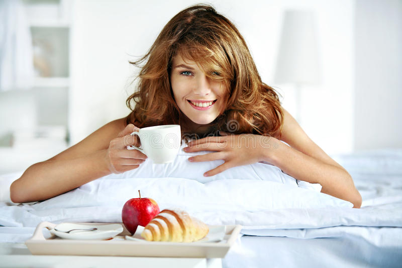 Dinner in bed. Beautiful brunette woman holding white porcelain cup in hand and smiling lying in bed stock photos