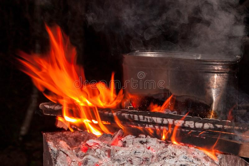 Dinner at the camping. kettle on a burning fire, fire, smoke. preparing a meal on a trip. wild rest. Dinner at the campsite. kettle on a burning fire, fire royalty free stock photography