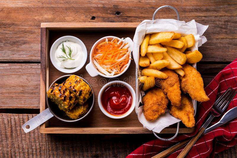 Dinner - chicken strips, french fries, roasted corn and salad royalty free stock photo