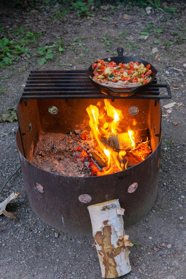 Dinner cooking over open camping fire cast iron skillet bacon and veggies stock photo