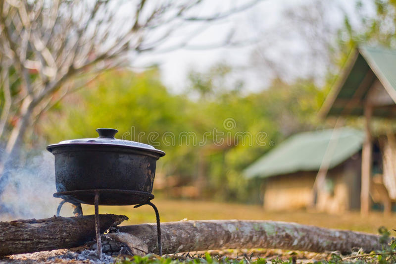 Dinner cooks in a large pot over an open fire stock images