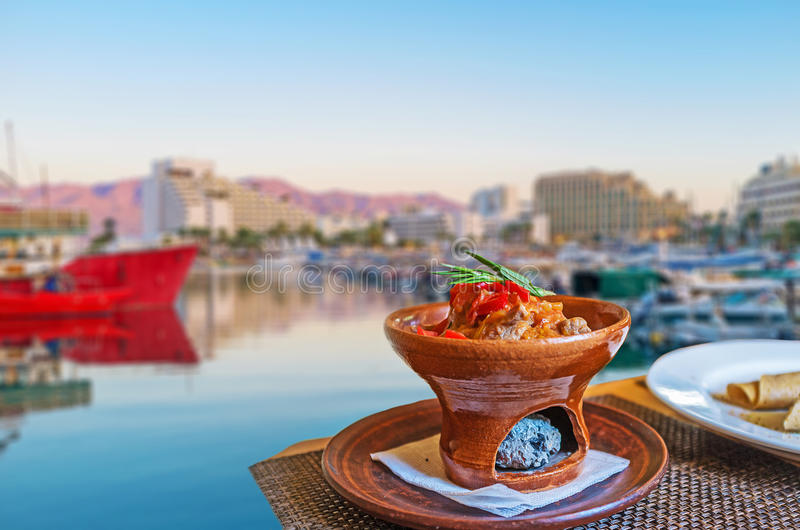 The dinner in Eilat marina. The dinner in restaurant of marina on sunset - the Eastern style beef in a dish with burner, Eilat, Israel royalty free stock photography