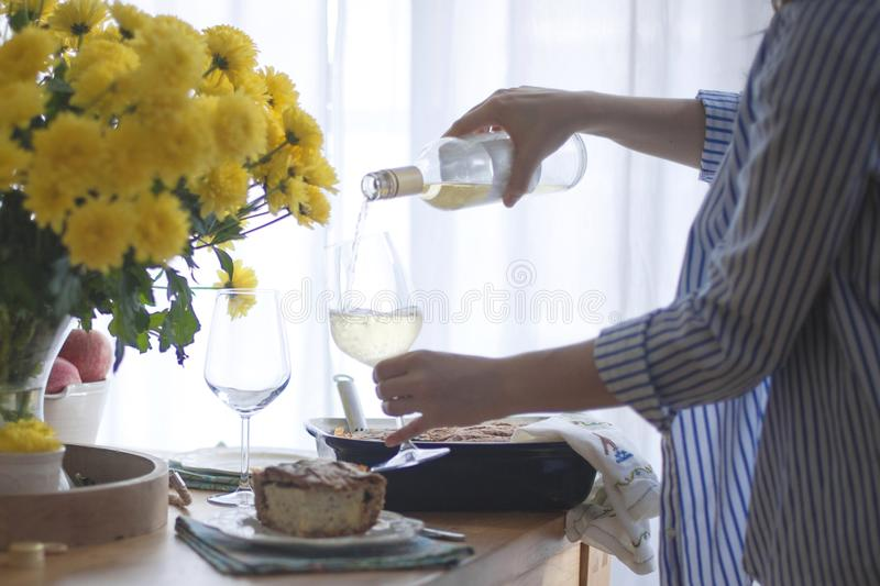 Dinner for the family. woman giving portions of food and wine. served table. yellow flowers on the table. table near the window royalty free stock image