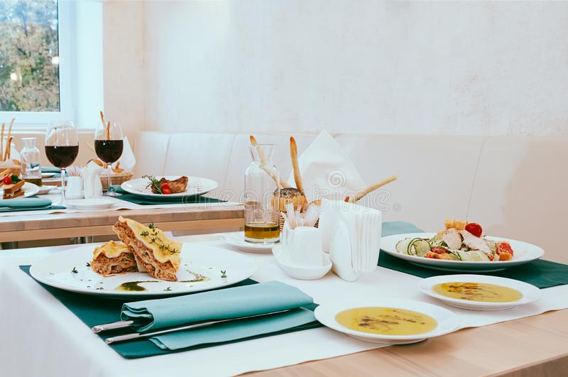 Dinner food served in restaurant, cute setup with meal and wine glasses royalty free stock image