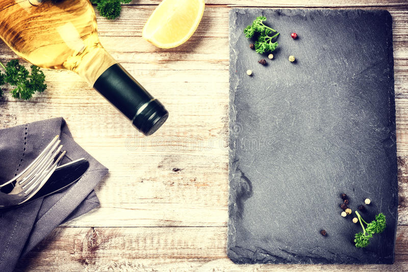Dinner frame with bottle of white wine and cutlery on wooden tab royalty free stock photo