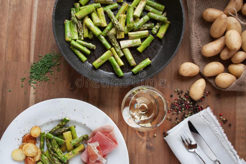 Dinner with fried asparagus and ham royalty free stock image