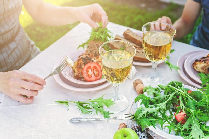Dinner in the garden. People eat at the table with wine, grilled fish, fresh vegetables and herbs. Horizontal shot stock photography