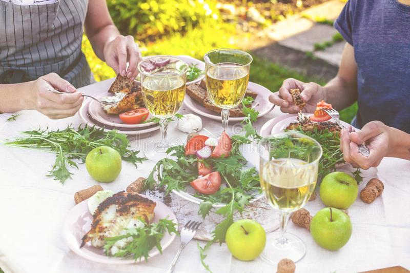 Dinner in the garden. People eat at the table with wine, grilled fish, fresh vegetables and herbs. Horizontal shot royalty free stock images